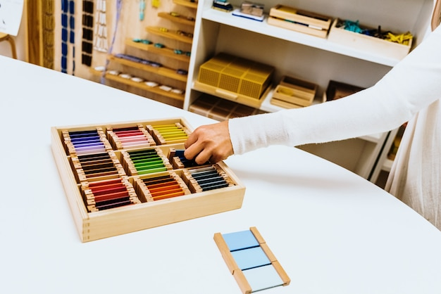 Hand eines studenten, der montessori material innerhalb eines klassenzimmers behandelt.