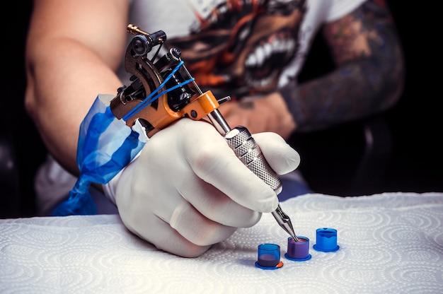 Hand eines tätowiermeisters und einer tätowiermaschine.