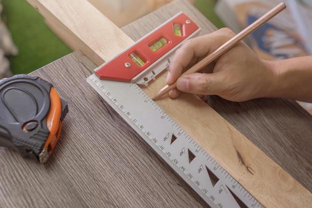 Hand eines tischlers misst den abstand unter verwendung des quadrats eines erbauers