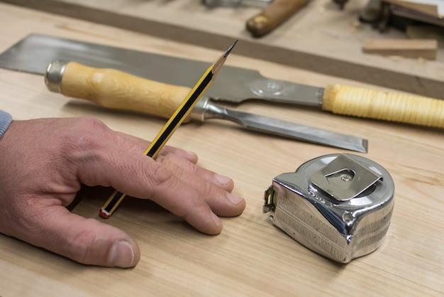Hand eines tischlers mit einem bleistift