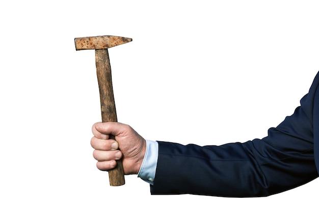 Hand eines tragenden anzugs des starken geschäftsmannes, der einen alten rostigen hammer lokalisiert auf dem weißen hintergrund hält. seitenansicht.