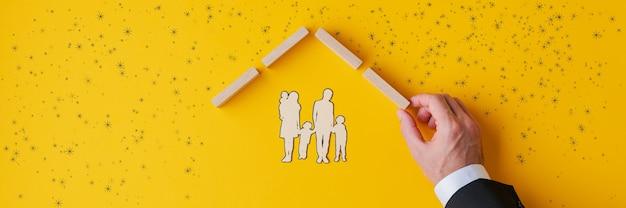 Hand eines versicherungsagenten, der eine papierschnitt-silhouette einer familie schützt, indem er ein dach aus holzstiften in einem konzeptuellen bild von versicherung und immobilien baut.