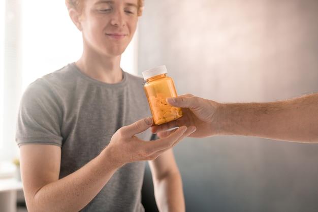 Hand eines zeitgenössischen physiotherapeuten, der eine flasche pillen an junge patienten weitergibt, die nach einem schweren unfall oder einer verletzung eine körperliche rehabilitation benötigen