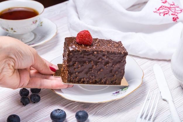 Hand ergreifendes stück beerenschokoladenkuchen verziert mit erdbeere auf hölzernem weißem hintergrund