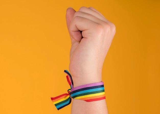 Hand erhöhtes regenbogenarmband, lgbt, schwuler stolz, auf pastellgelbem hintergrund