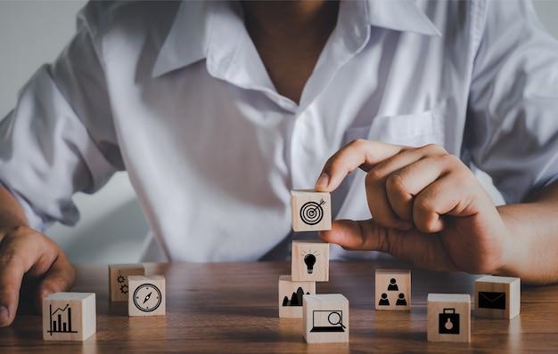 Hand erwachsener asiatischer mann, der dartscheibe-symbol auf würfelblock hält. unternehmensführung, finanzen, strategie, marketing. holzblock mit symbolen konzept. personalmanagement, strategiezielplanung.