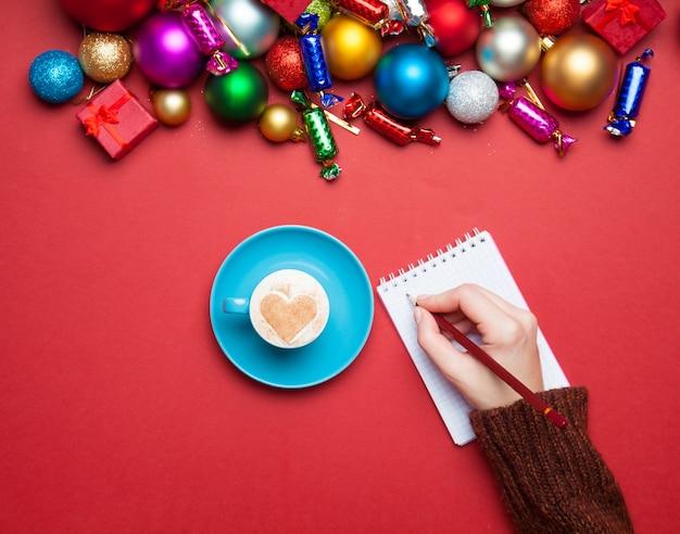 Hand etwas in das notizbuch in der nähe von weihnachtsspielzeug schreiben.