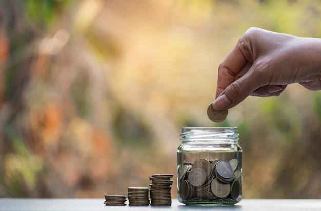Hand fallen lassen eine münze mit geldmünzstapel, der für geschäft wächst.