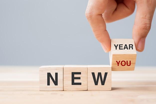 Hand flip holzblock mit neujahr zu neuem text auf tabellenhintergrund. lösungs-, gesundheits-, plan-, ziel-, geschäfts- und urlaubskonzepte