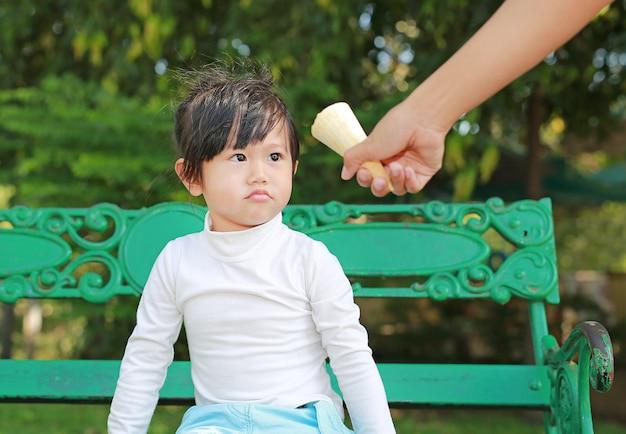 Hand gegebene eiscreme zu einem kind, kleines mädchen, das auf bank im park sitzt