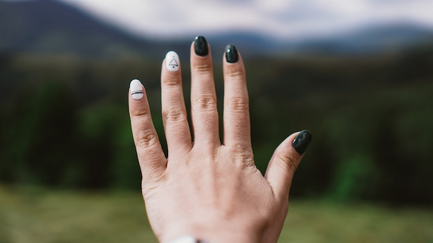 Hand gegen berg. weibliche hand vorwärts. bergtal. natürliche sommerlandschaft.