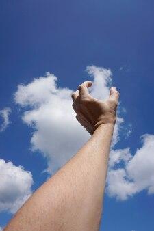Hand gestikulierte in den blauen himmel