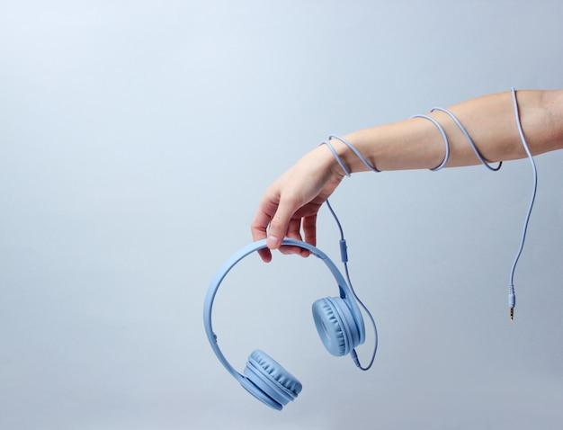 Hand gewickeltes kabel hält blaue kopfhörer auf blauem hintergrund