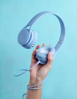 Hand gewickeltes kabel hält kopfhörer auf blauem hintergrund