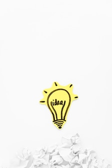 Hand gezeichnete glühlampe der idee mit zerknittertem papier auf weißem hintergrund