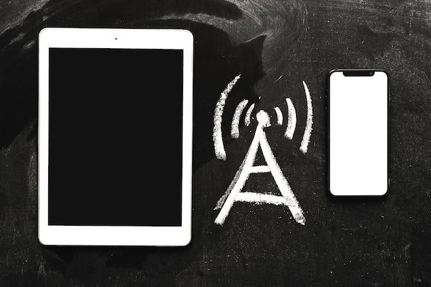Hand gezeichnete netzsignalikone zwischen der digitalen tablette und dem mobiltelefon auf tafel