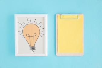 Hand gezeichneter Glühlampenrahmen und -klemmbrett mit gelbem Papier