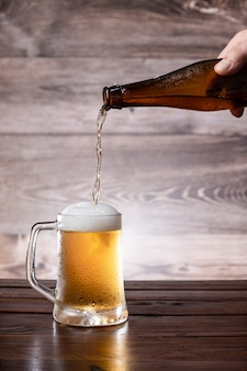 Hand gießen bier in einen kalten krug auf holzbasis.