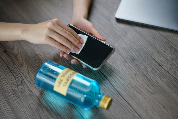Hand gießen ethylalkohol aus der flasche in ein baumwollstück für sauberes handy