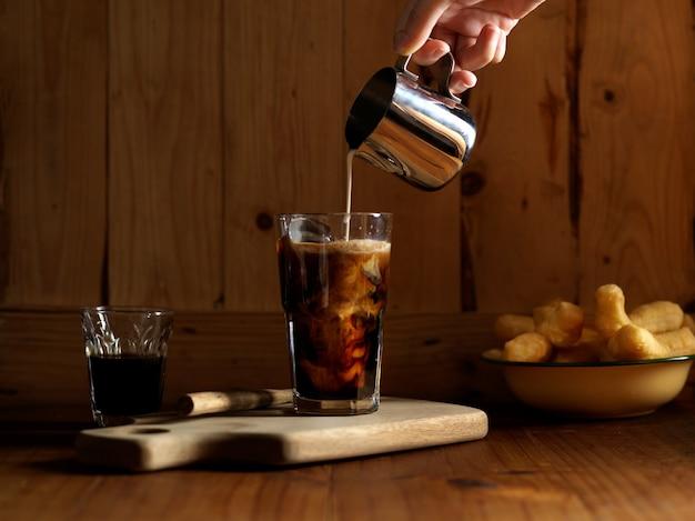 Hand gießen milch in eiskaffee auf holztisch mit frittierten teigstangen
