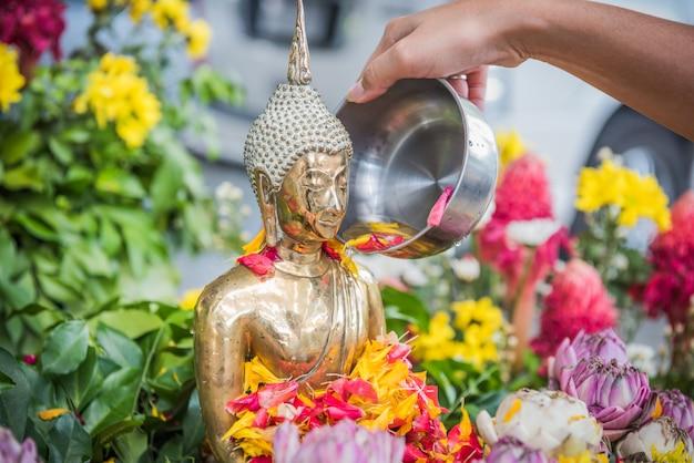 Hand gießen wasser die buddha-statue anlässlich des songkran-festivaltages