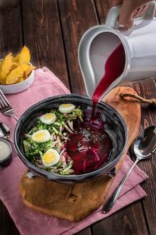 Hand gießt aus einer alten rote-bete-wurzeln suppe des weißen krugs mit eiern. ofenkartoffeln, soße, rosa tischdecke auf dem rustikalen hölzernen hintergrund. ansicht von oben