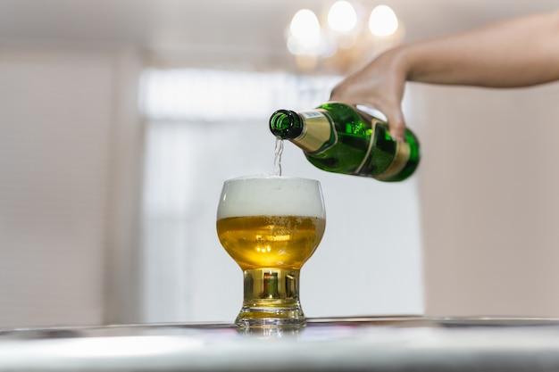 Hand gießt bier aus grüner flasche in glas.