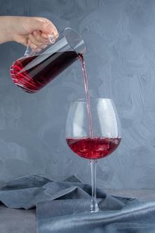 Hand gießt granatapfelsaft in eine glasschale mit eiswürfeln