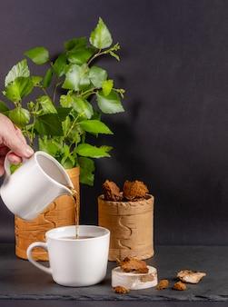 Hand gießt heilgetränk von birkenpilz chaga in weiße keramikschale auf schwarz. vertikales foto. speicherplatz kopieren.