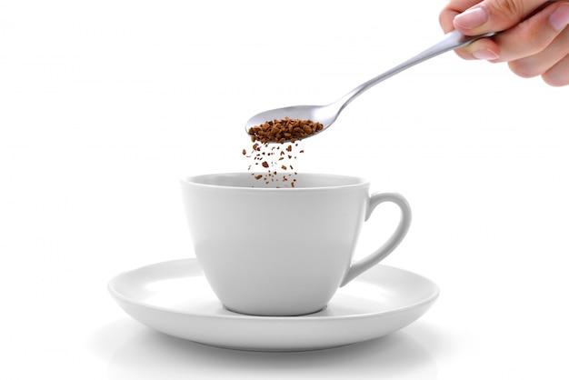Hand gießt instantkaffee aus einem löffel in eine kaffeetasse
