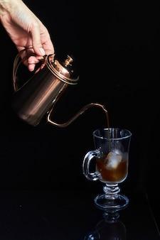 Hand gießt kaffee aus kupfer kaffeekanne in glasschale