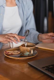 Hand gießt milch in eine tasse kaffee