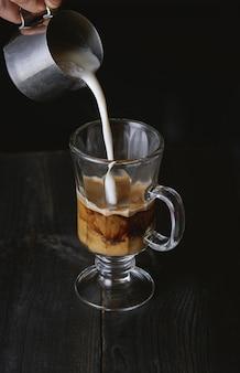 Hand gießt milch in kaltem brühkaffee auf schwarzem holztisch.