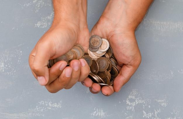 Hand gießt münzen in eine andere.