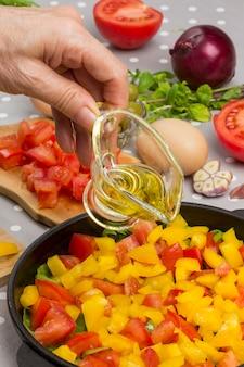 Hand gießt öl. in scheiben geschnittene tomaten und gemüse in der pfanne. eier, oliven, knoblauch, gelber pfeffer auf dem tisch.
