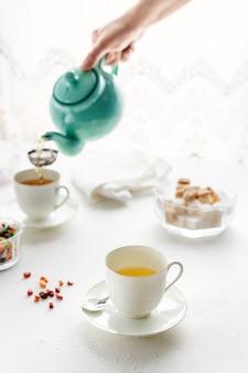 Hand gießt tee in teetassen