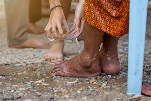 Hand gießt wasser auf den fuß der verehrten ältesten und bittet um segen glücklich