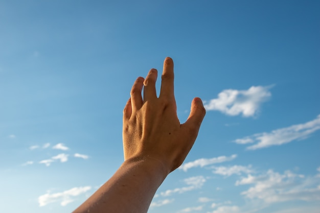 Hand greift nach dem himmel