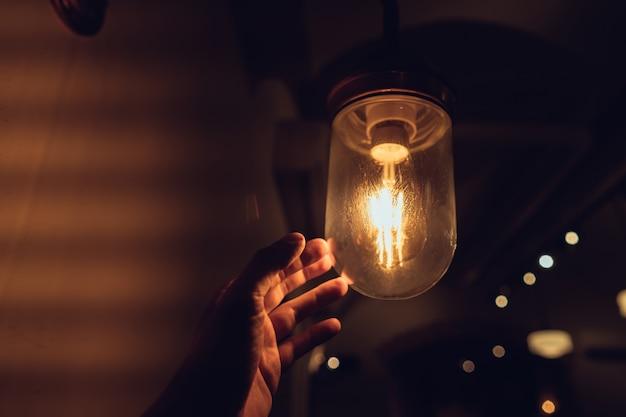 Hand greift nach einer vintage glühbirne.