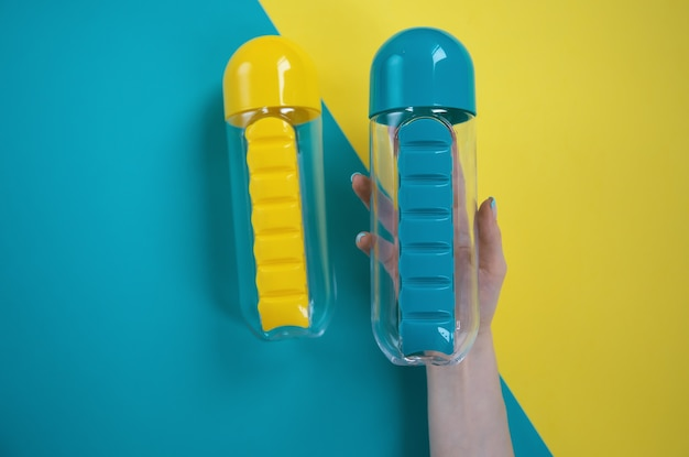 Hand hält blaue und gelbe wasserflaschen auf blauem und gelbem hintergrund