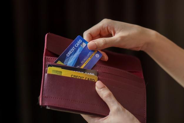 Hand hält brieftasche und kreditkarte herausnehmen.