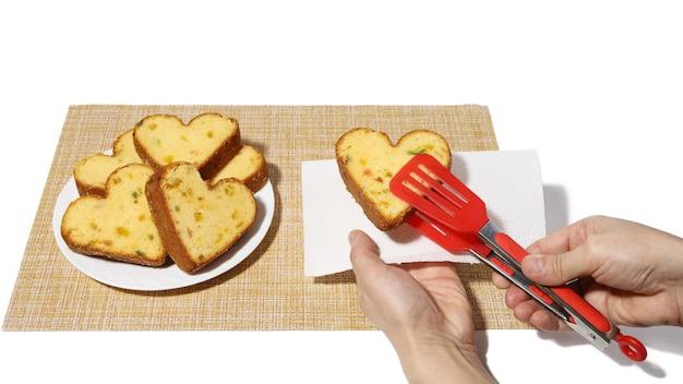 Hand hält clip mit herzförmigem cupcake und legt ihn auf serviette in der anderen hand