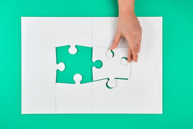 Hand hält das fehlende element im puzzlespiel auf einem grün