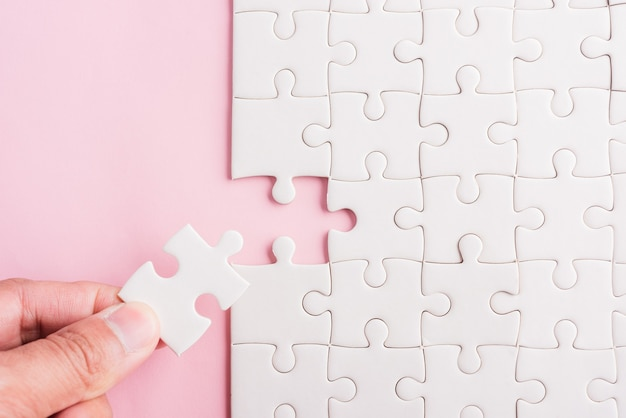 Hand hält das letzte stück des puzzlespiels