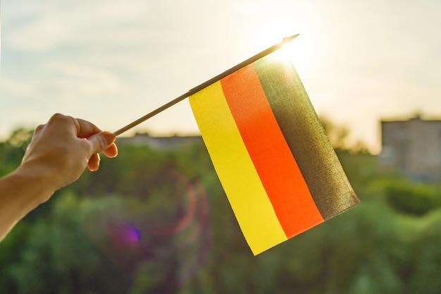 Hand hält deutschland flagge ein offenes fenster