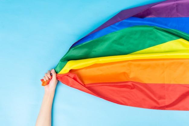 Hand hält die regenbogenfahne
