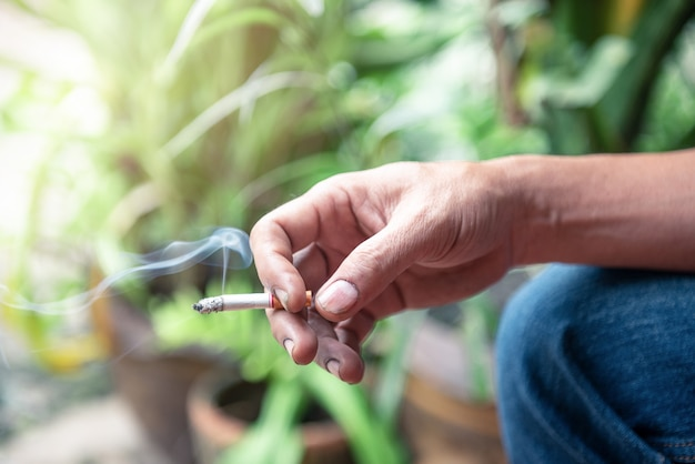 Hand hält die zigarette mit rauch