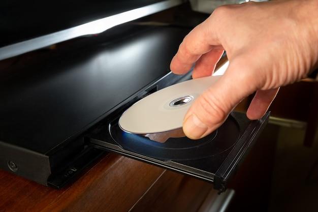 Hand hält dvd-disk-insert zum dvd-player