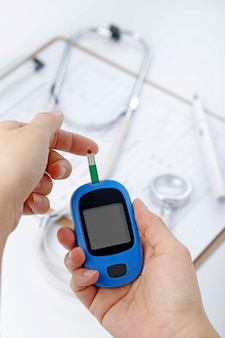 Hand hält ein blutzuckermessgerät messung blutzucker, ist der hintergrund ein stethoskop und chart-datei
