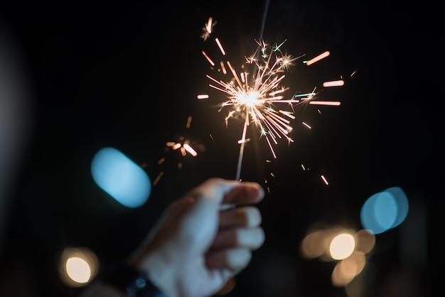 Hand hält ein brennendes wunderkerzenlicht